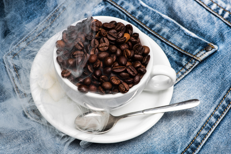 Cup with coffee beans, refined sugar and spoon on plate, denim background. Mug full of coffee beans on jeans and cloud of smoke. Freshly roasted coffee concept