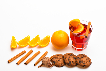 Drink or beverage with orange and cinnamon. Cocktail and bar concept. Mulled wine near slices of orange. Glass with mulled wine or hot cider near orange slices and cookies on white background Stock Photo