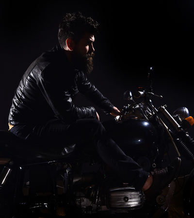 Macho, brutal biker in leather jacket riding motorcycle at night time, copy space. Bikers leisure concept. Man with beard, biker in leather jacket sitting on motor bike in darkness, black background