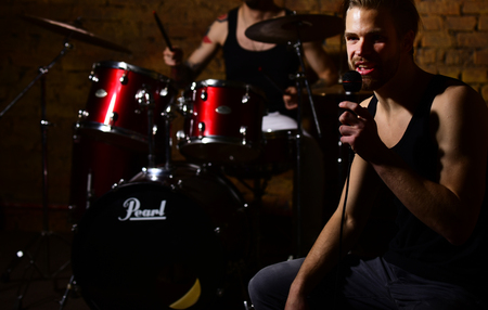 Guy with microphone sings in studio or bar. Stock Photo