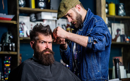 Hipster lifestyle concept. Barber with clipper trimming hair on temple of client. Hipster client getting haircut. Barber with hair clipper works on hairstyle for bearded man barbershop background