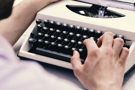 Writer typing with retro writing machine. Old typewriter