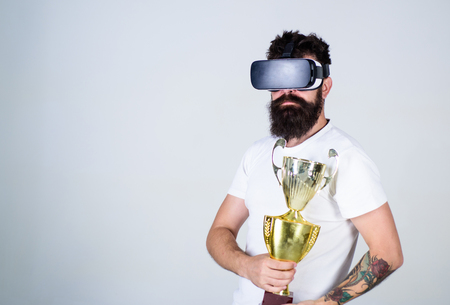Man with nerdy beard in VR headset isolated on gray background. Bearded man holding 1st prize. Hipster with trendy beard and mustache won contest. Champion of online games tournament, gaming concept