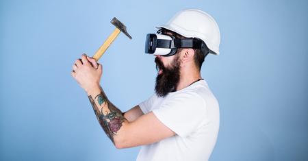 Hipster busy with renovation in virtual reality. Man with beard in VR glasses holds hammer, light blue background. Guy with HMD hammering virtual nail into VR surface. Builder and renovation concept Stock Photo