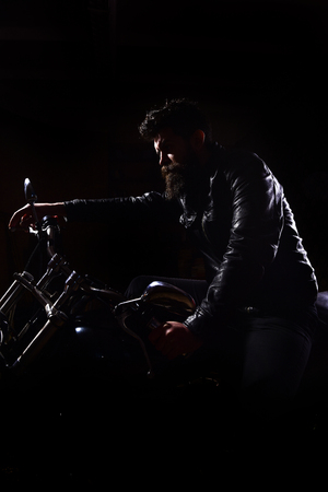 Night racer concept. Macho, brutal biker in leather jacket riding motorcycle at night time, copy space. Man with beard, biker in leather jacket sitting on motor bike in darkness, black background 版權商用圖片
