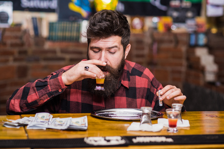 Guy spend leisure in bar getting high, defocused background.