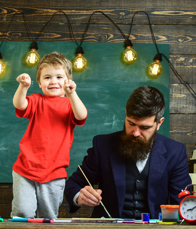 Child cheerful and teacher painting, drawing. Art lesson concept. Teacher with beard, father teaches little son to draw in classroom, chalkboard on background. Talented artist spend time with son Stok Fotoğraf