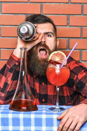 Man in checkered shirt holds shaker in front of eye, brick wall background. Barman and cocktails concept. Barman with long beard and stylish hair with cheerful face near alcoholic cocktail, close up