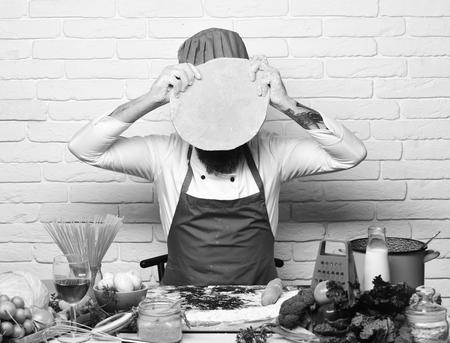 Le chef tient la pâte roulée. L'homme étend la pâte à pizza