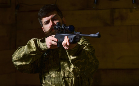 Man with beard wears camouflage clothing, wooden interior background. Macho on strict face at gamekeepers house. Huntsman concept. Hunter, brutal hipster with gun aiming before hunting, copy space Stock fotó