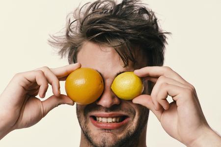 Man with orange and lemon instead of eyes in hands Reklamní fotografie