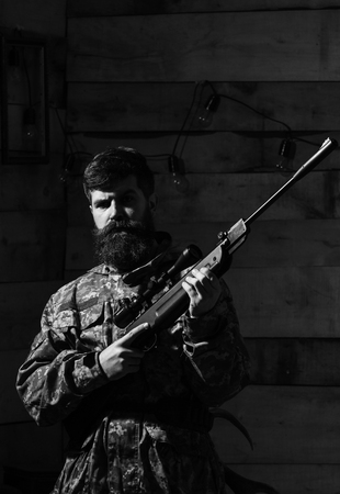 Huntsman concept. Man with beard wears camouflage clothing, wooden interior background. Macho on strict face at gamekeepers house. Hunter, brutal hipster with gun prepare rifle for hunting, copy space