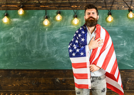 Patriotic education concept. American teacher covered with american flag. Man with beard and mustache on serious face with flag of USA, chalkboard on background. Teacher teaches to love homeland, USA Stockfoto