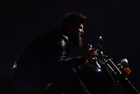Man with beard, biker in leather jacket sitting on motor bike in darkness, black background. Masculinity concept. Macho, brutal biker in leather jacket riding motorcycle at night time, copy space Stock Photo