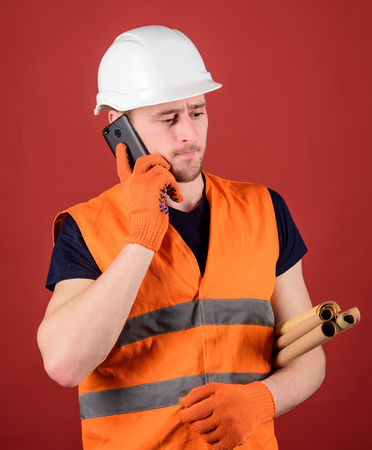 Engineer, architect, builder on busy face speaks on smartphone while holds blueprints. Architect concept. Man, foreman in helmet supervises construction on phone, red background 版權商用圖片