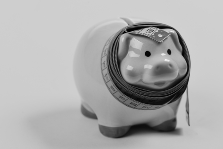saving money. Ceramic toy pig with blue flexible ruler on yellow background Stock Photo