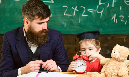Individual education concept. Teacher and pupil in the classroom. Little boy learning the time. Cute kid in graduation cap examining the clock Banco de Imagens