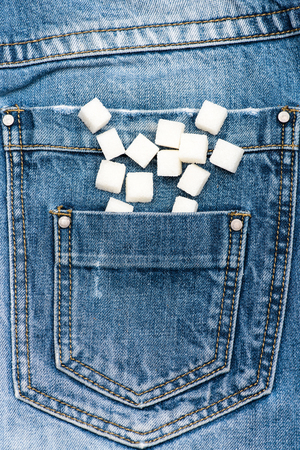 Refined sugar on denim background. Pocket of jeans full of refined sugar. Diet concept. Pocket full of sugar as symbol of high calorie unhealthy nutrition 写真素材