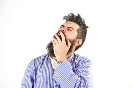 Morning yawning concept. Guy covering mouth with hand, copy space.