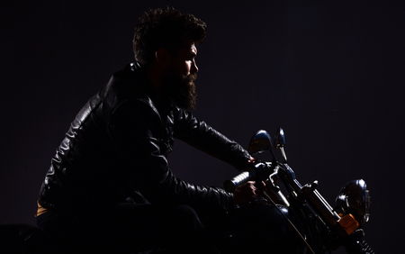 Macho, brutal biker in leather jacket riding motorcycle at night time, copy space. Man with beard, biker in leather jacket sitting on motor bike in darkness, black background. Masculinity concept