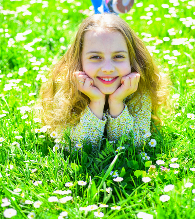 Heyday concept. Girl on smiling face spend leisure outdoors. Girl lying on grass at grassplot, green background. Child enjoy spring sunny weather while lying at meadow Фото со стока