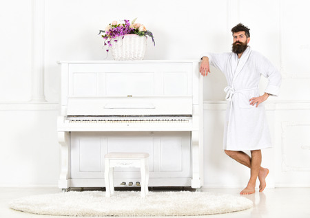 Man with beard in bathrobe enjoys morning while standing near piano. Talented musician concept. Man serious stands and leans on piano musical instrument in white interior on background