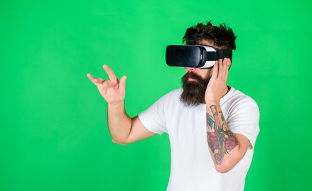 Man with long beard in VR goggles watching 3D show. Brutal bearded man enjoying recorded rock concert. Man with tattoo and stylish beard raving about 360 video of favorite band, digital era concept Banco de Imagens
