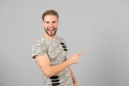 Guy bearded attractive pointing index finger to side. Advice concept. Man cheerful happy face looks successfully, grey background. Man with beard unshaven guy looks handsome well groomed