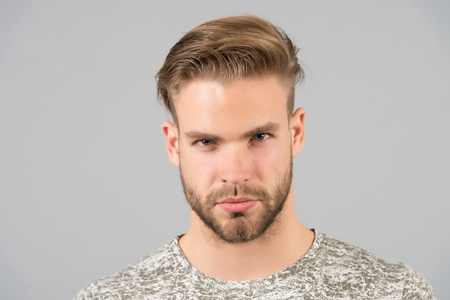 Man bearded confident face, grey background. Skin care concept. Man bearded unshaven guy looks handsome and well groomed. Guy attractive cares about his appearance. Macho with smooth healthy skin