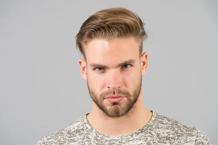 Homme barbu visage confiant, fond gris. Concept de soins de la peau. L'homme barbu non rasé a l'air beau et bien soigné. Guy attractive se soucie de son apparence. Macho avec une peau lisse et saine