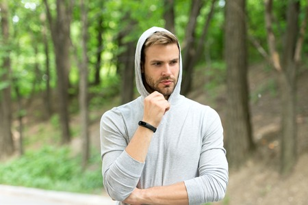 Sportsman training with pedometer gadget. Fitness tracker concept. Man athlete on pensive face with sport fitness gadget, nature background. Athlete with bristle with fitness tracker or pedometer