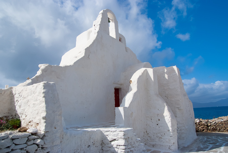 Church of Panagia Paraportiani in Mykonos, Greece. Chapel building with small bell tower. White church architecture on cloudy blue sky. Religion and cult concept. Vacation on mediterranean island Reklamní fotografie