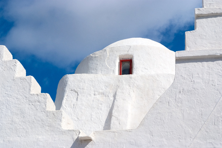 Church dome with small window in Mykonos, Greece. Chapel building architecture detail. White church on cloudy blue sky. Religion and cult concept. Summer vacation on mediterranean island