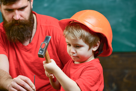 Boy, child busy in protective helmet learning to use hammer with dad. Fatherhood concept. Father with beard teaching little son to use tools, hammering, chalkboard on background