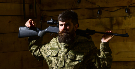 Masculinity concept. Hunter, brutal hipster on strict face with gun ready for hunting. Man, gamekeeper with beard wears camouflage clothing, carries rifle on shoulders, wooden interior background