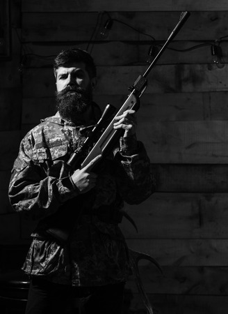 Hunter, brutal hipster with gun ready for hunting. Macho on strict face at gamekeepers house. Huntsman concept. Man with beard wears camouflage clothing, wooden interior background