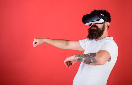 Man with beard in VR glasses driving car, red background. Virtual driving lessons concept. Hipster on confident face driving car in virtual reality with modern digital gadget