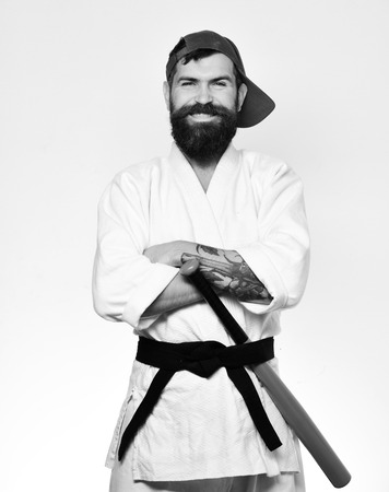 Karate man with smiling face puts green baseball bat behind black belt. Man with beard in white kimono and green cap