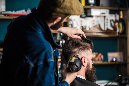 Hipster bearded client getting hairstyle. Barber with hairdryer drying and styling hair of client. Barber with hairdryer works on hairstyle for bearded man, barbershop background. Styling concept