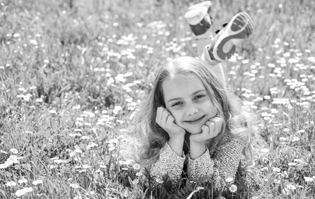 Girl lying on grass at grassplot, green background, copy space. Girl on smiling face spend leisure outdoors. Heyday concept. Child enjoy spring sunny weather while lying at meadow