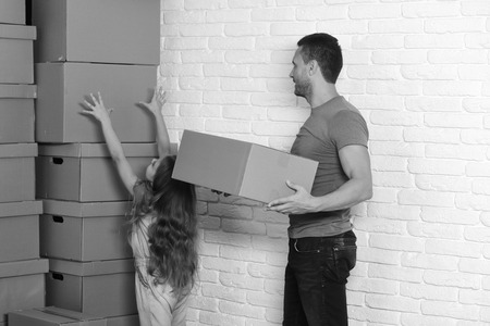 Kid and guy move into new home or move out Girl and man with busy faces on white wall background