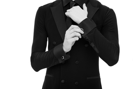 Hands adjust sleeve. Fashionable caucasian male isolated on white background. Formal suit or tuxedo. Used to perfection. Everything should be stylish, black and white