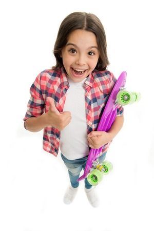 Joyful and happy. Kid girl casual style with penny board enjoy childhood. Girl joyful happy with skateboard isolated white. Hobby and leisure concept. Child likes skateboarding show thumb up gesture