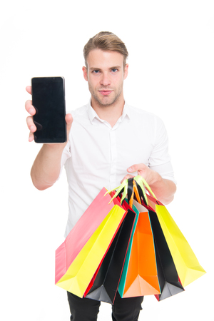 Guy buy fashionable clothes online with smartphone. Man happy client received packages purchases. Online shopping concept. Man takes advantages online shopping. Guy carries bunch colorful bags Stock Photo