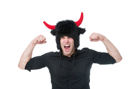 Feeling so angry. Man shouting face wears hat of devil with horns. Guy black shirt angry aggressive demonstrate strength gesture. Man emotional screaming. Guy angry as devil isolated white background