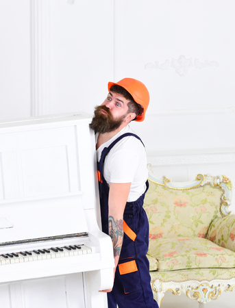 Bearded workman lifting piano with great force. Builder removing stuff before home renovation isolated on white background.