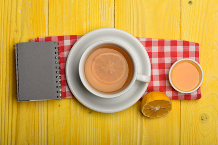 Warm drink and home atmosphere concept. Hot beverage with citrus slices on napkin on yellow wooden background. Cup of green tea with slice of lemon. Tea cup with honey and little notebook, top view