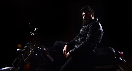 Man with beard, biker in leather jacket sitting on motor bike in darkness, black background. Macho, brutal biker in leather jacket riding motorcycle at night time, copy space. Night racer concept Stock Photo