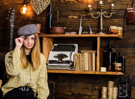 Girl in casual outfit with kepi in wooden vintage interior. Lady on calm face in plaid clothes looks cute and casual. Tomboy concept. Girl tomboy spend time in house of gamekeeper