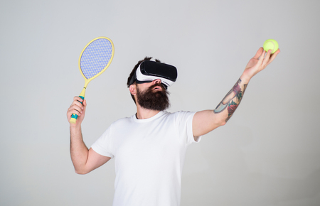 Handsome man in virtual reality headset playing tennis, grey background. Hipster use modern technology for sport games. Guy with VR glasses play tennis with racket and ball. Virtual tennis concept